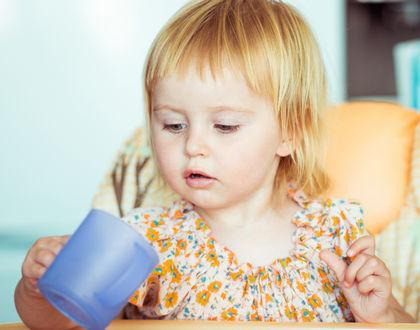 девочка пьет из кружечки