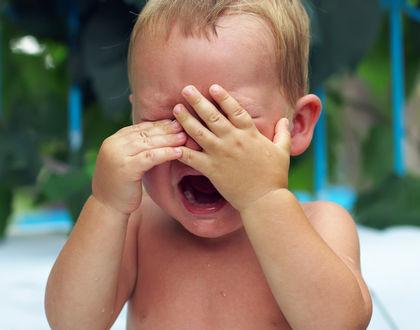 ребенок плачет и закрыл лицо руками