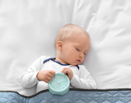 спящий ребенок с будильником