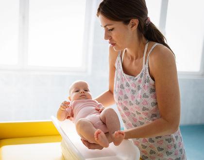 мама взвешивает малыша