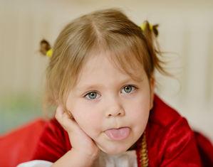 девочка показывает язык