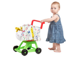 Девочка учится ходить с тележкой