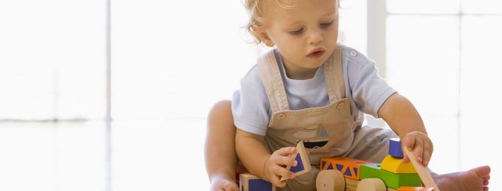 Малыш играет и с деревянным поездом