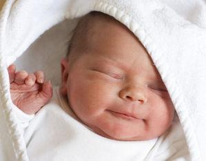Новорожденный спит в пледе