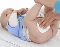 Новорожденного протирают ватным диском