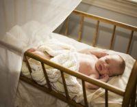 Ребенок спит в своей кроватке