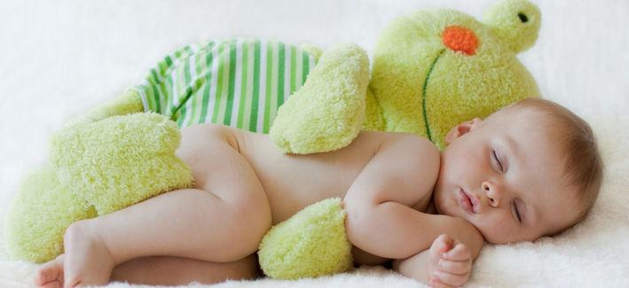 Ребенок спит рядом с игрушкой