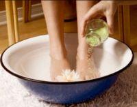 Женщина парит ноги в тазике