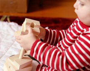 ребенок играет с деревянной игрушкой