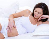 Беременная женщина лежит и смотрит на живот